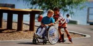 Boy (6-8) in-line skating, pushing friend in wheelchair