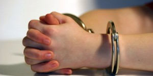 Child's hands in handcuffs resting on table